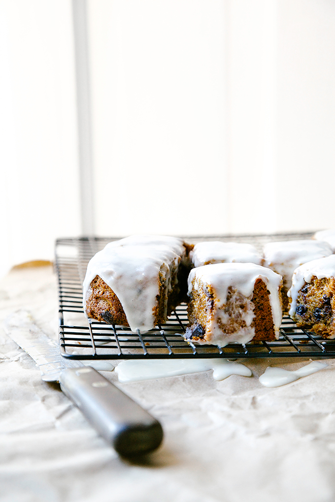 Squares of ginger cake with icing on cooling rack, with knife.