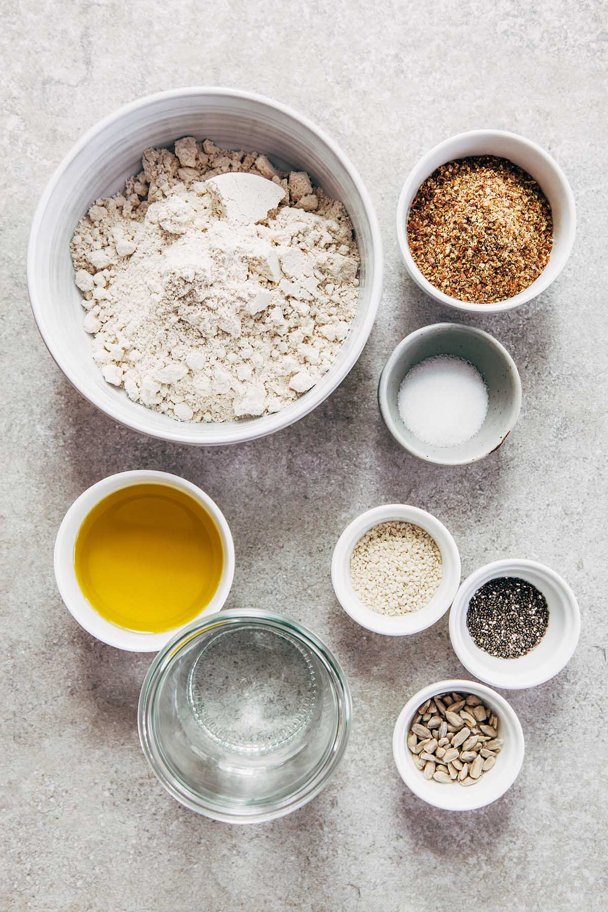Ingredients to make oat crackers laid out on a table in small dishes.