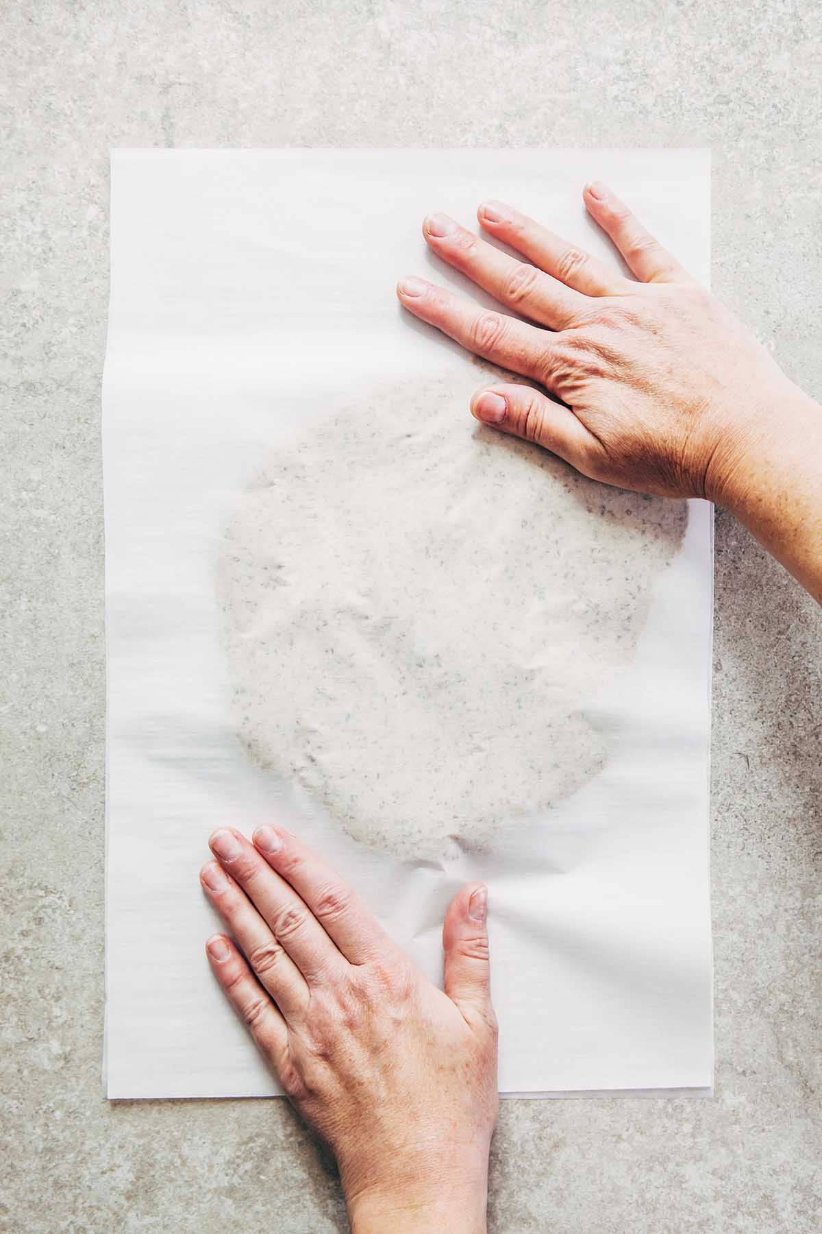 Two hands flattening dough between two pieces of parchment paper.