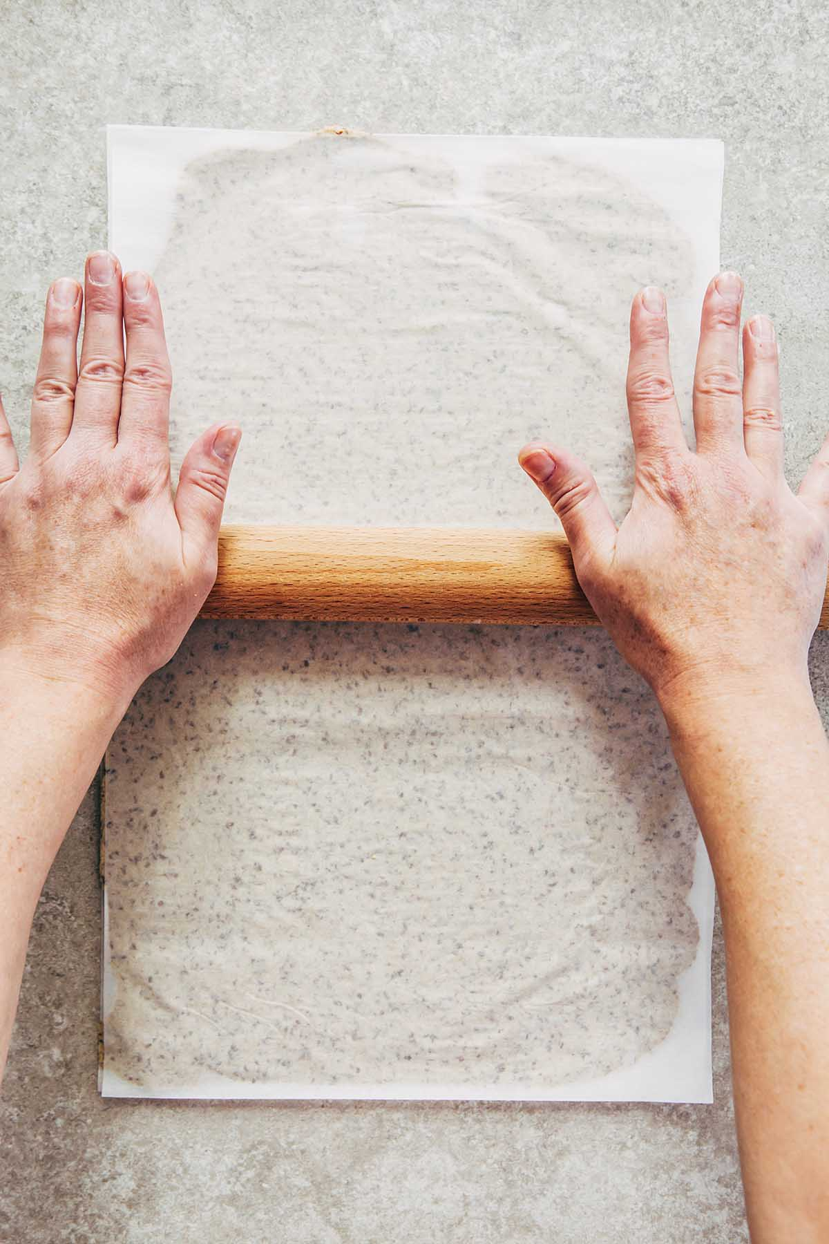 Two hands using a rolling pin to smooth oat cracker dough between two pieces of parchment paper.