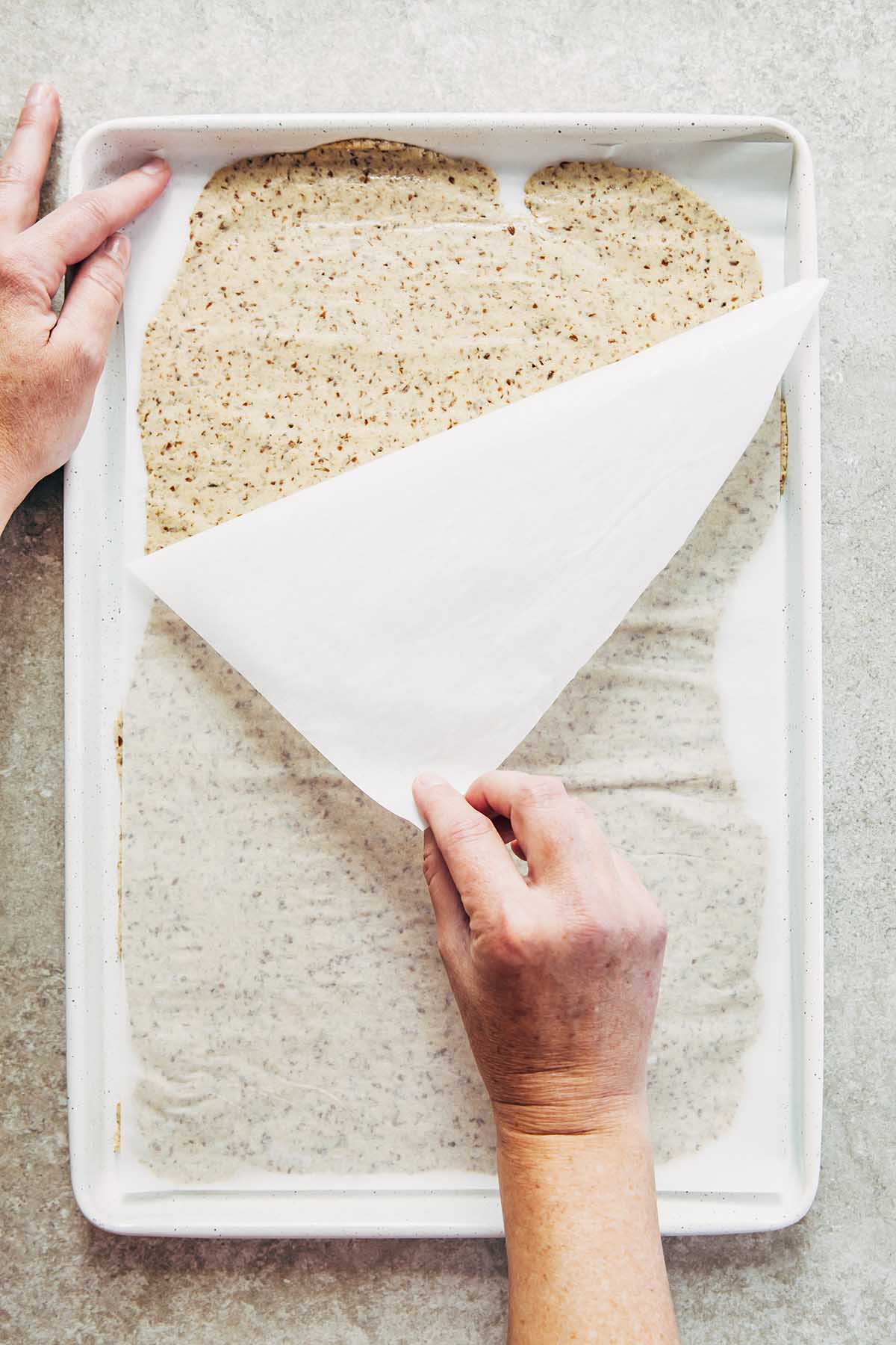 A hand peeling away the top layer of parchment paper from flattened dough.