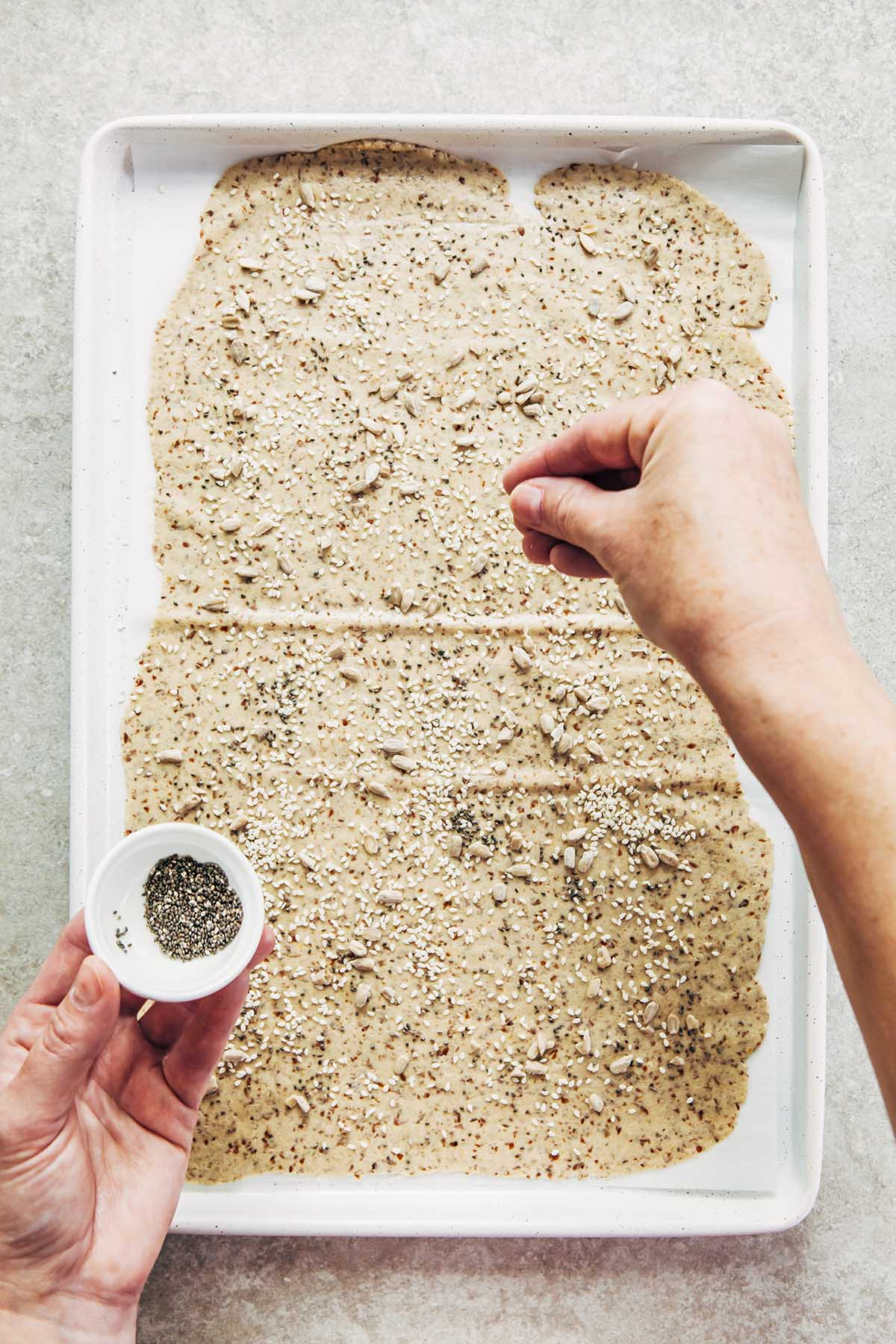 A hand sprinkling chia seeds from a small white bowl onto rolled cracker dough on a baking sheet.
