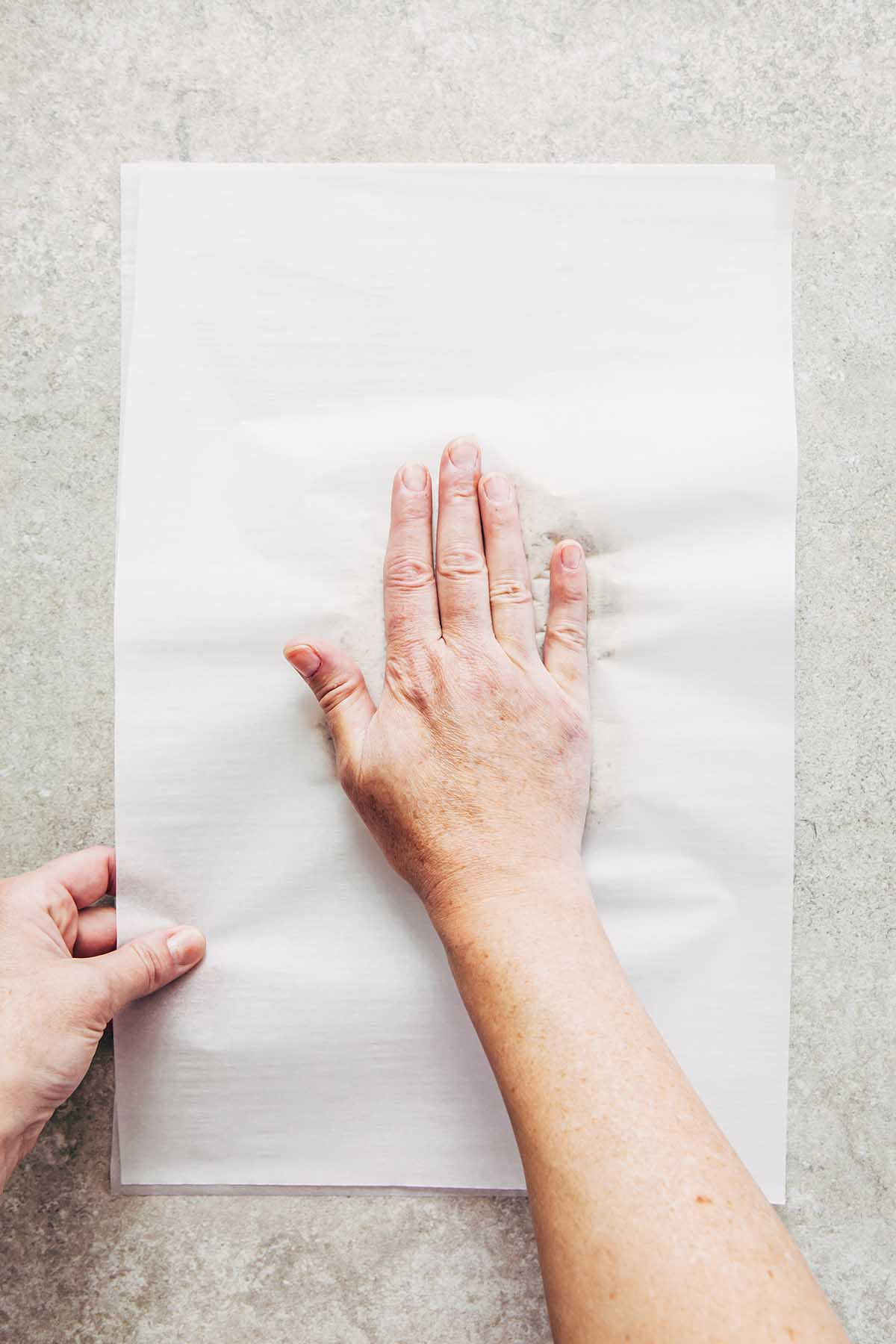 A hand flattening dough between two pieces of parchment paper.