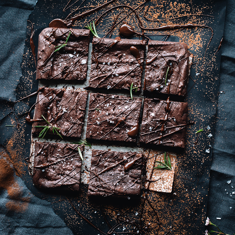 Overhead of spicy rosemary sea salt brownies garnished with fresh rosemary and cocoa powder.