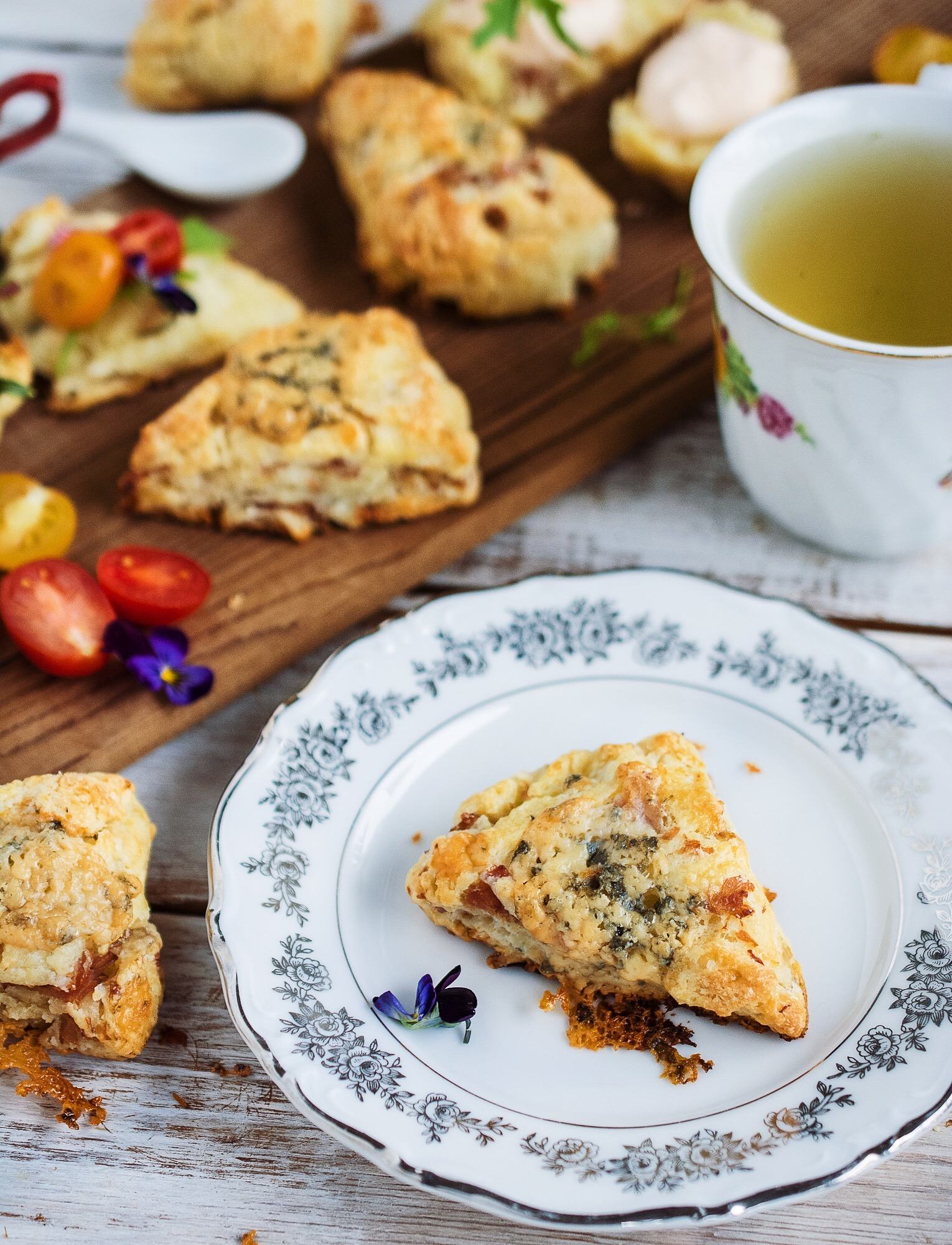 A ham and blue cheese scones on a plate next to a wooden board of scones.
