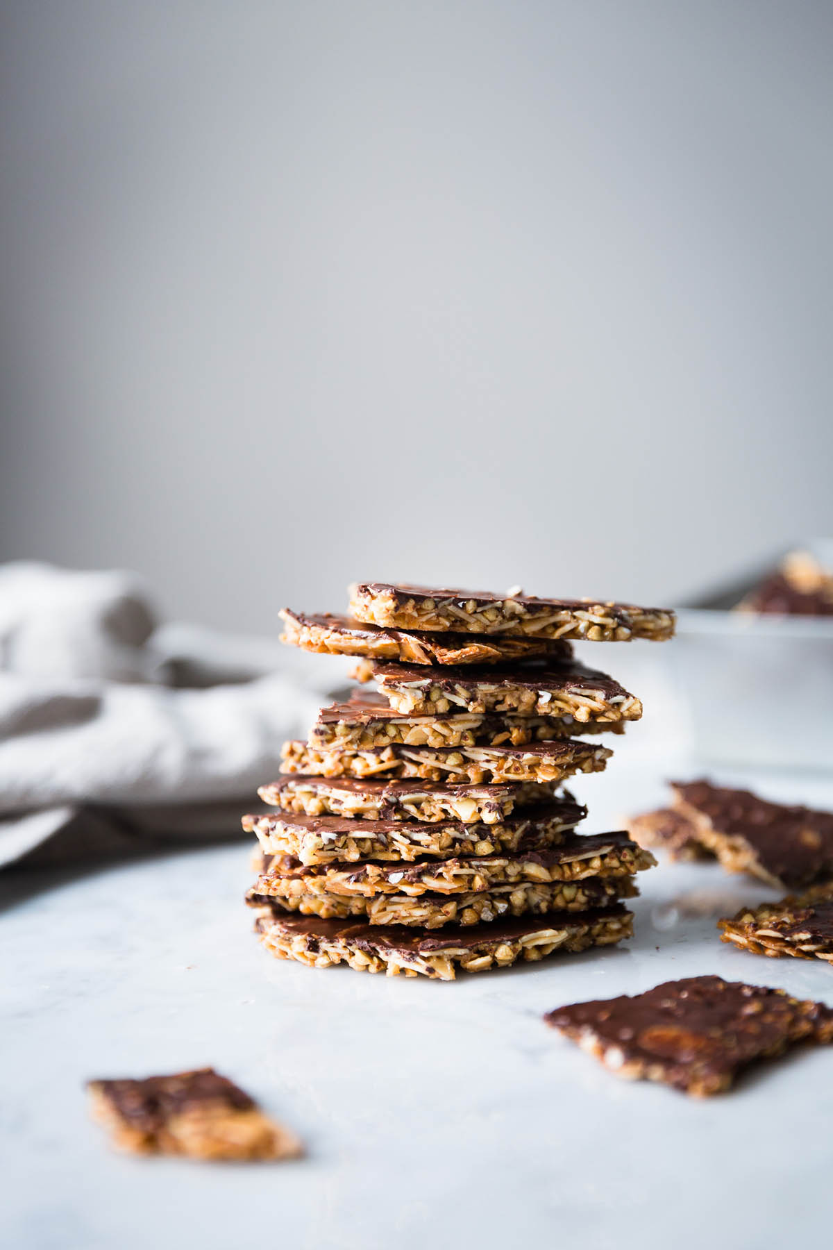 Vegan almond brittle stacked in a pile with more pieces beside.