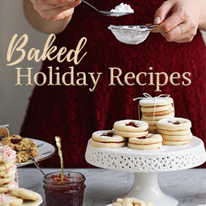 Woman sprinkling icing sugar on cake stand of cookies with text writing: Baked Holiday Recipes.