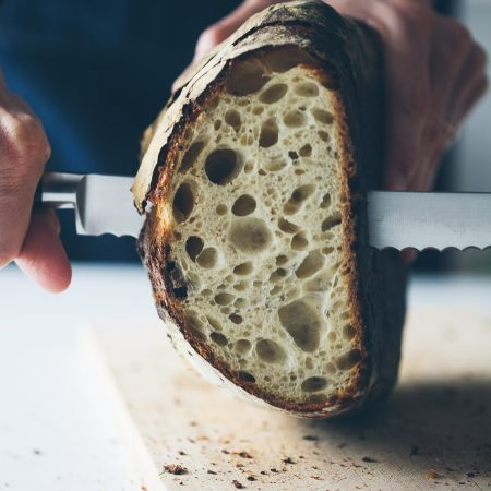 Straight on shot of sourdough bread being sliced. Very open crumb.