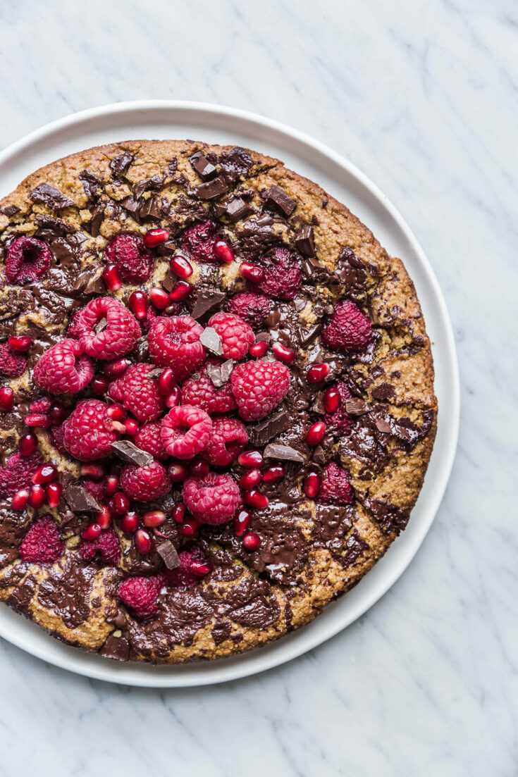 A large almond chocolate cake topped with raspberries on a plate.