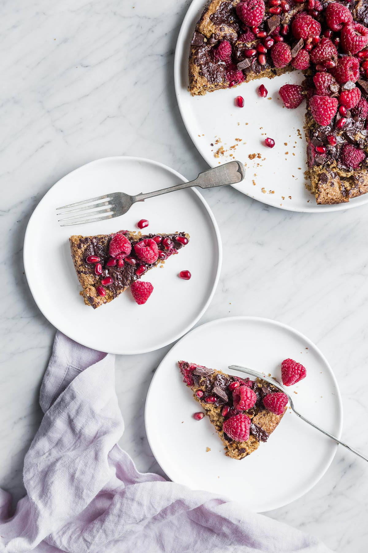 Two slices of cake topped with raspberries on plates.