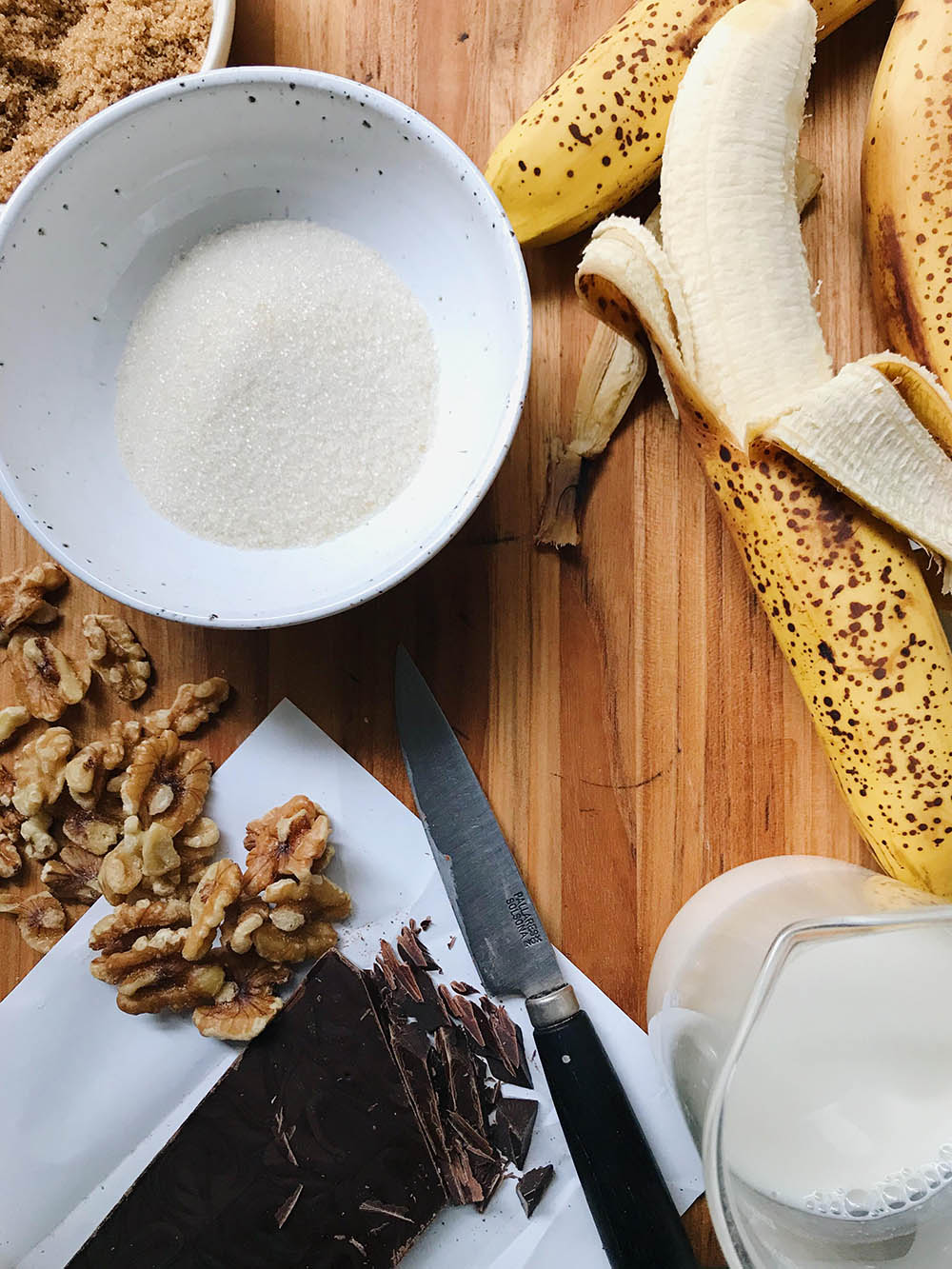 Banana bread ingredients on a wooden cutting board. Ripe banana, sugar, nuts, chocolate.