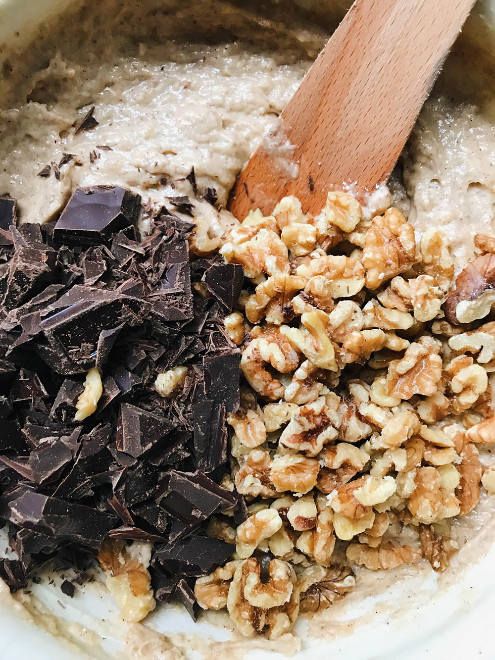 Banana bread batter with chopped chocolate and walnuts on top.