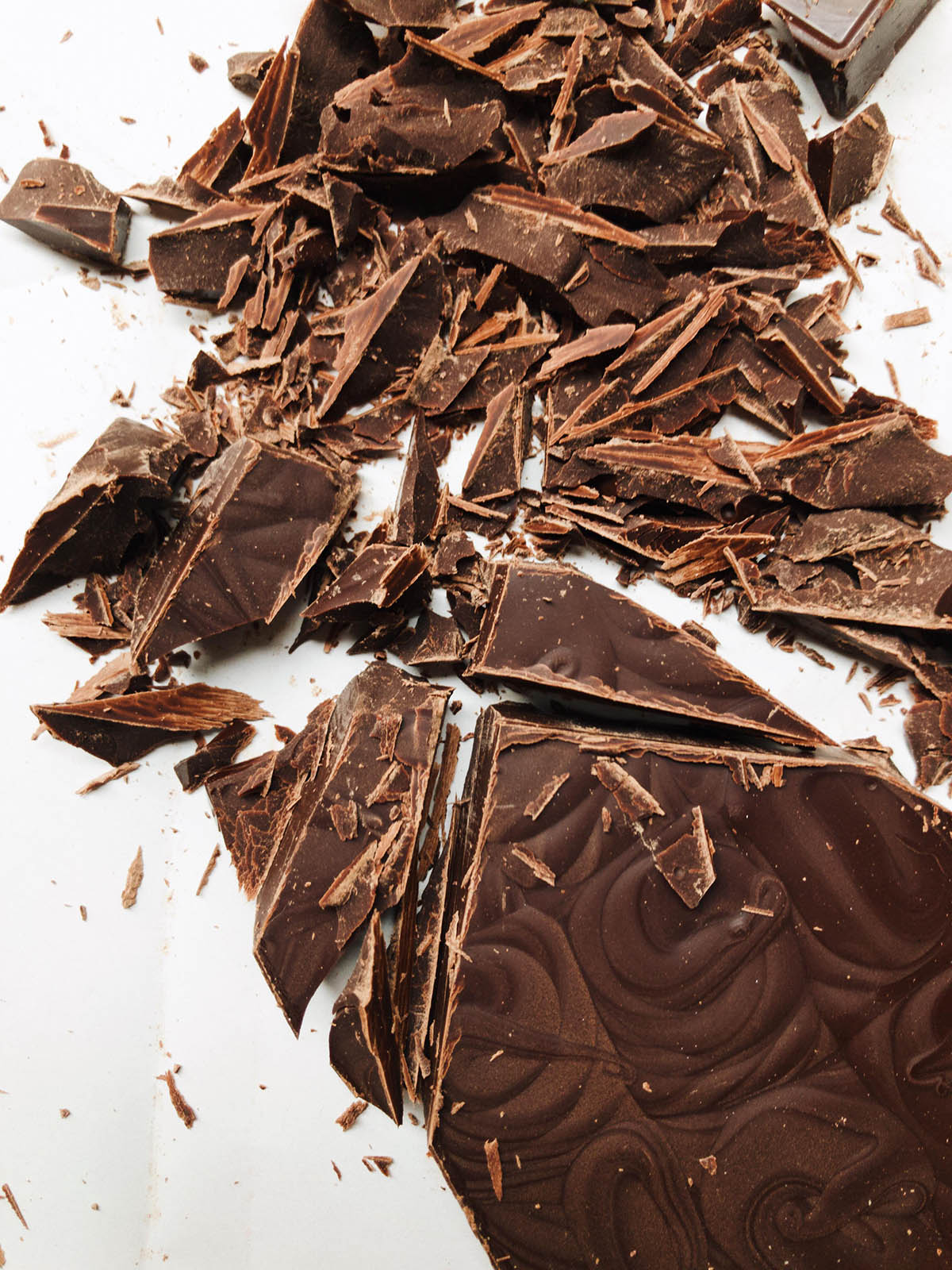 A bar of dark chocolate, partly chopped.