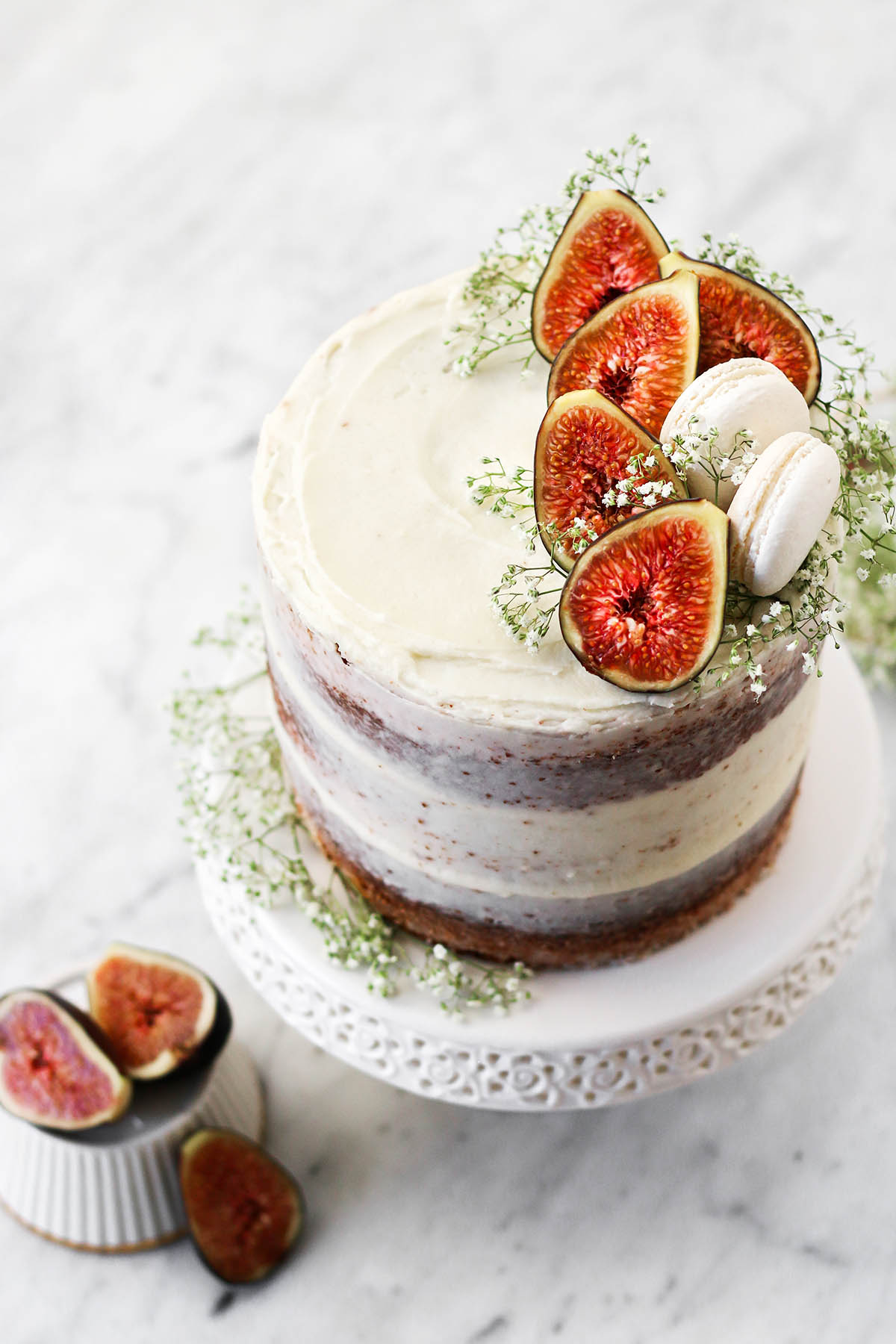 A tall layer cake on a white stand with cream cheese icing and fig topping.