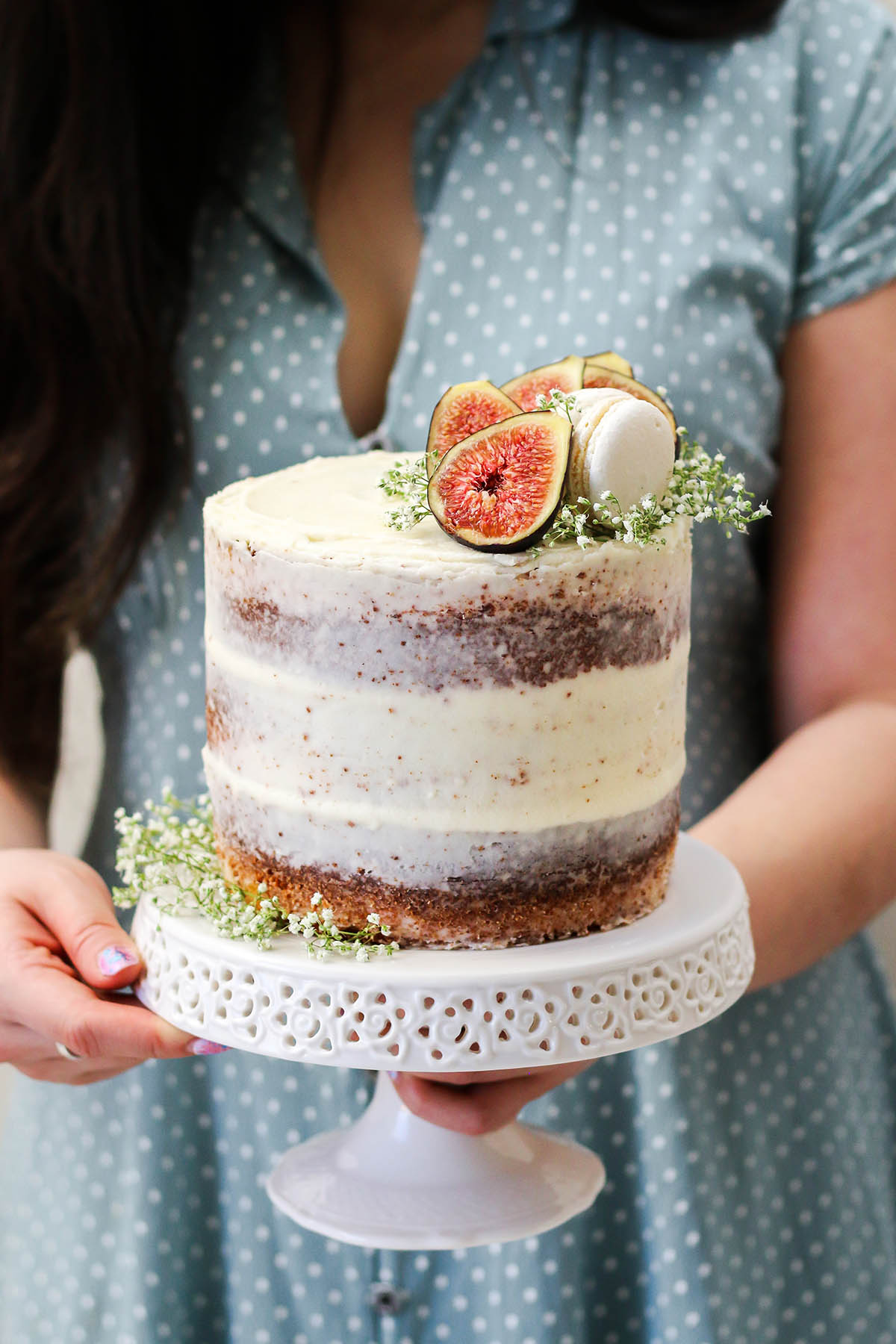 Woman in blue polka dot dress holding a layer cake on a white cake stand.