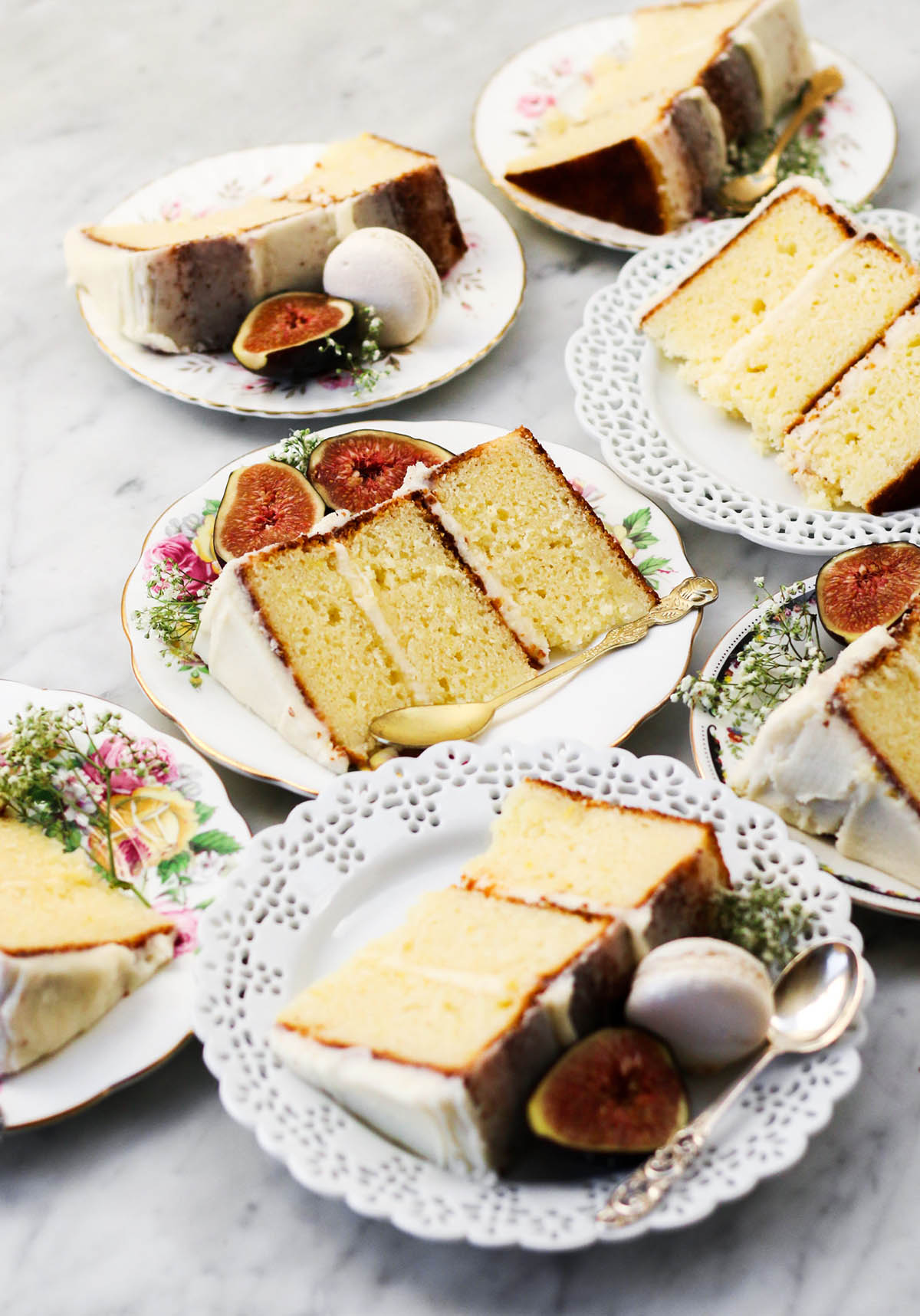 Several plates with floral motifs holding slices of cake with icing and figs.