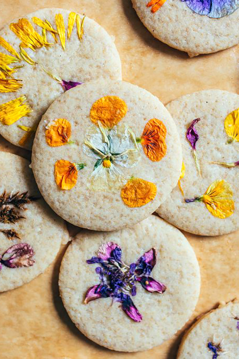 Close up over head shot of a cookies on parchment paper topped with flower petals.