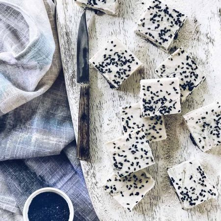 Overhead shot of small rounds of Frozen Tahini and Black Sesame Fudge on a cutting board
