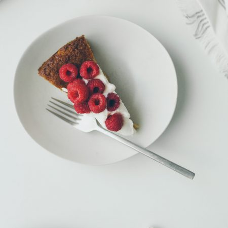Overhead shot of a piece of rhubarb cornmeal cake with maple cinnamon whipped cream and raspberries