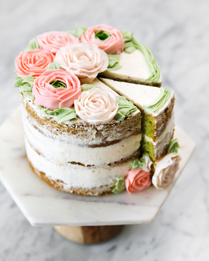 Layer cake with buttercream roses decorating, on marble cake stand, one slice cut.