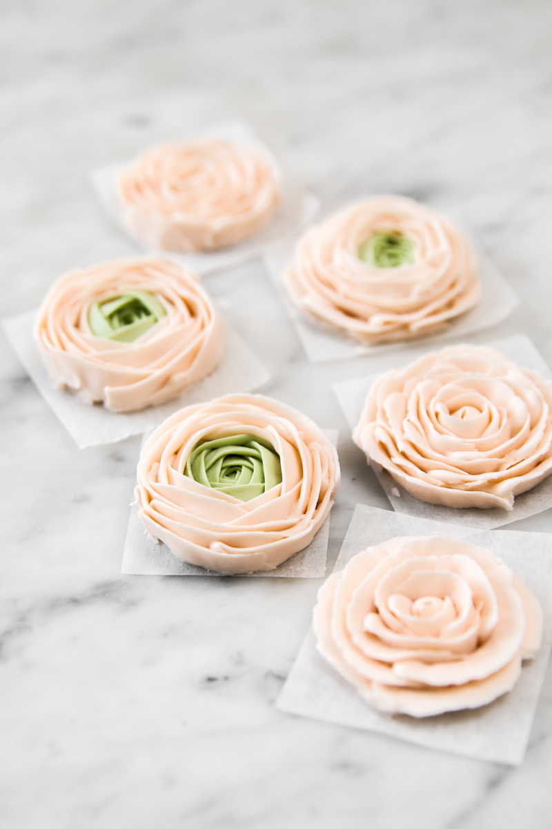 Pale pink and green buttercream roses on marble surface.