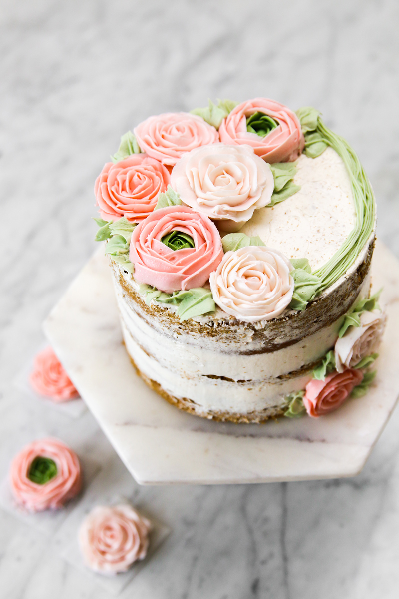 Layer cake with buttercream roses decorating, on marble cake stand.