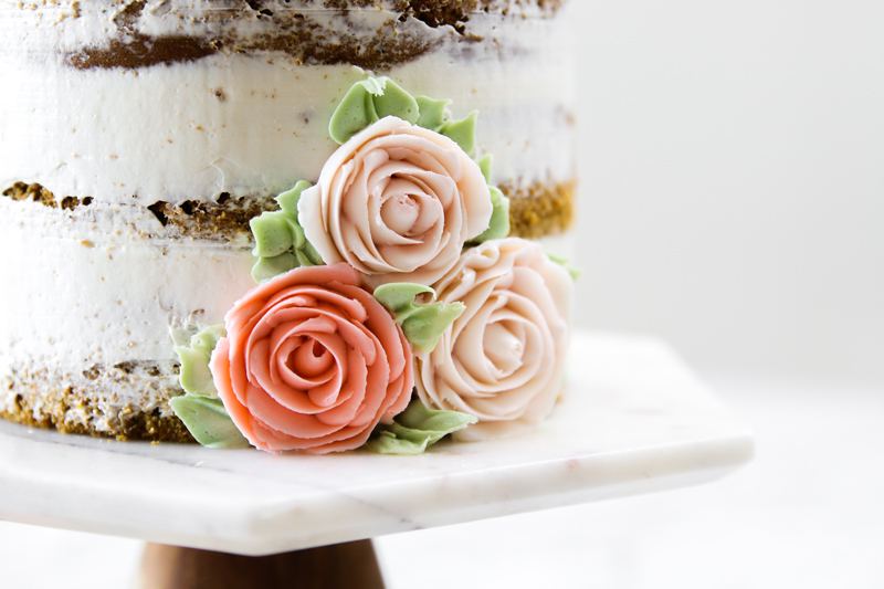 Close up of buttercream roses on side of layer cake.