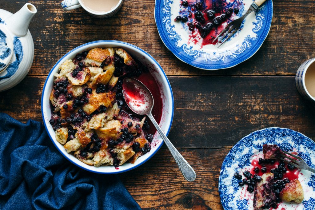 A dish of sourdough bread pudding with wild blueberries.
