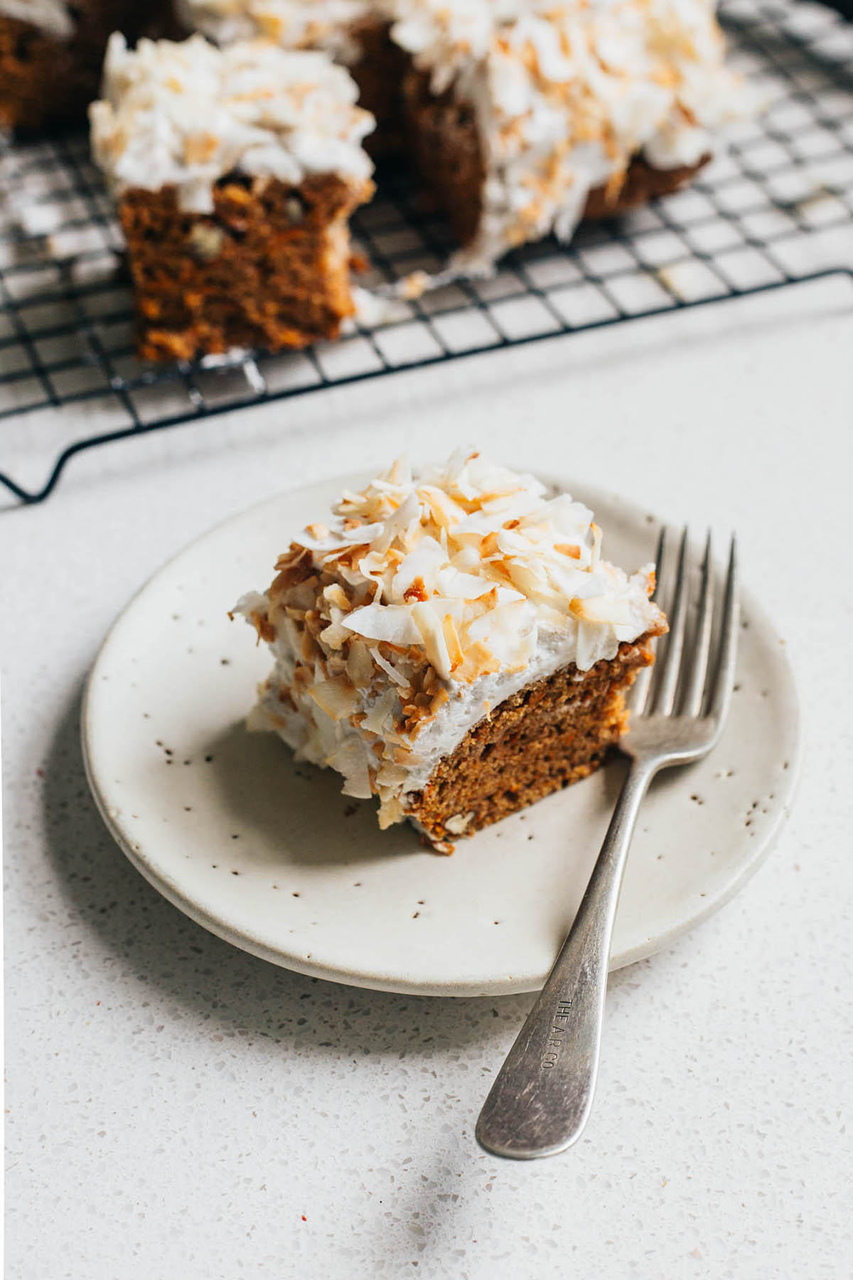 Square of carrot cake with icing on a small plate with fork, with more cake in the background.