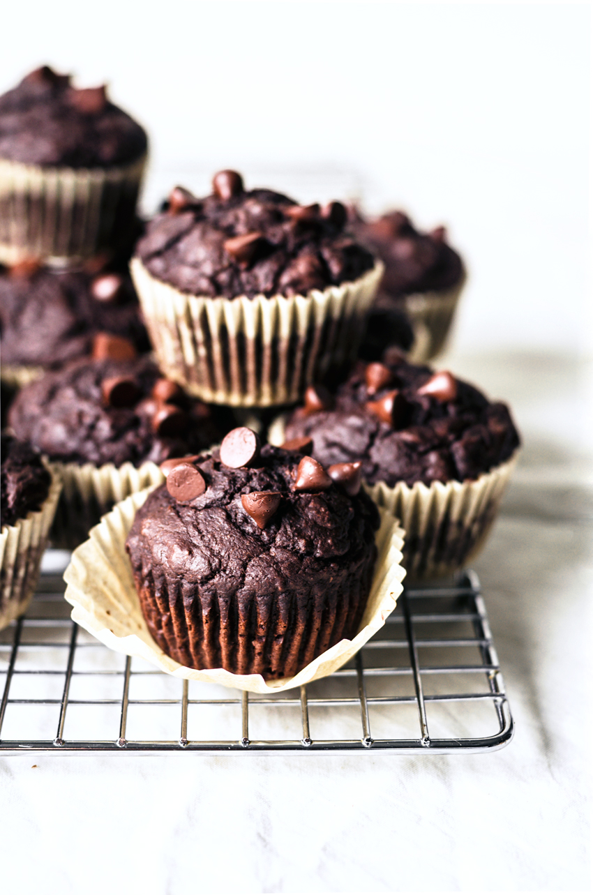 Vegan chocolate zucchini muffins with chocolate chips on cooling rack