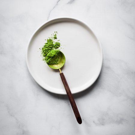 Matcha tea on a spoon on a white plate