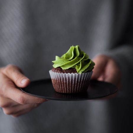 Vegan Chocolate Matcha Cupcakes head on held by hand on plate