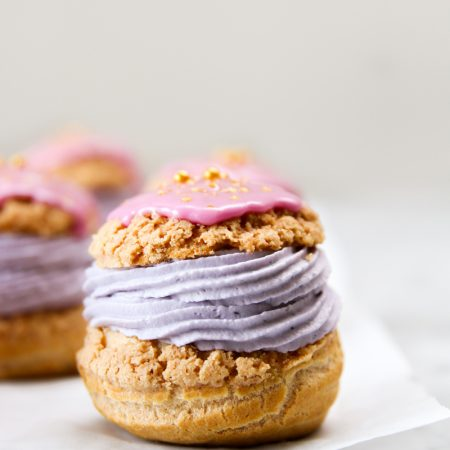 Cream puffed filled with purple cream and topped with pink glaze.