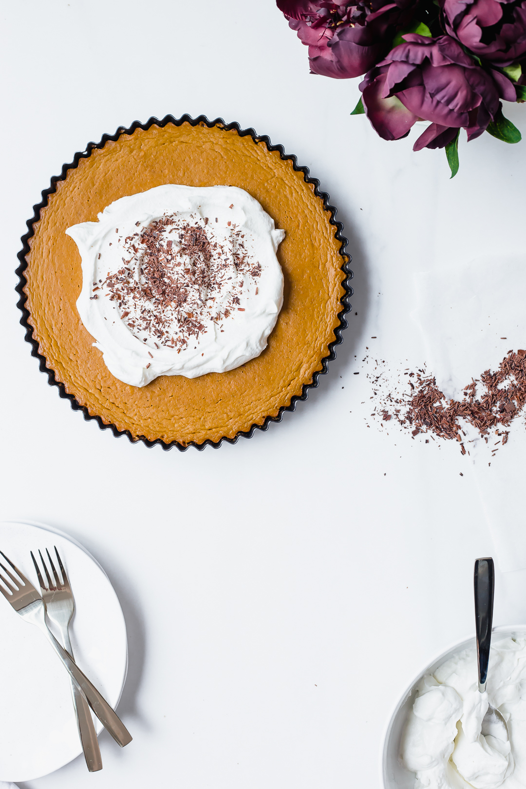 Overhead shot of Pumpkin Pie with chocolate cookie crust topped with whipped cream and chocolate shavings