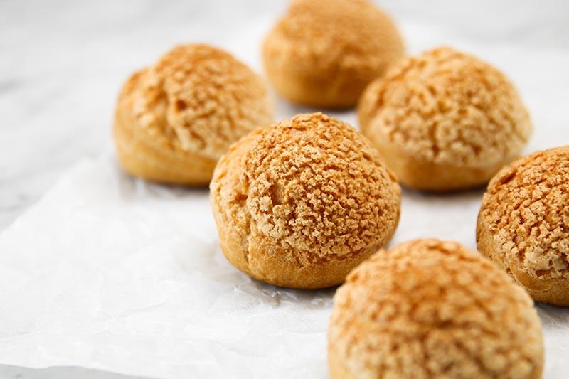 Choux pastry buns on parchment.