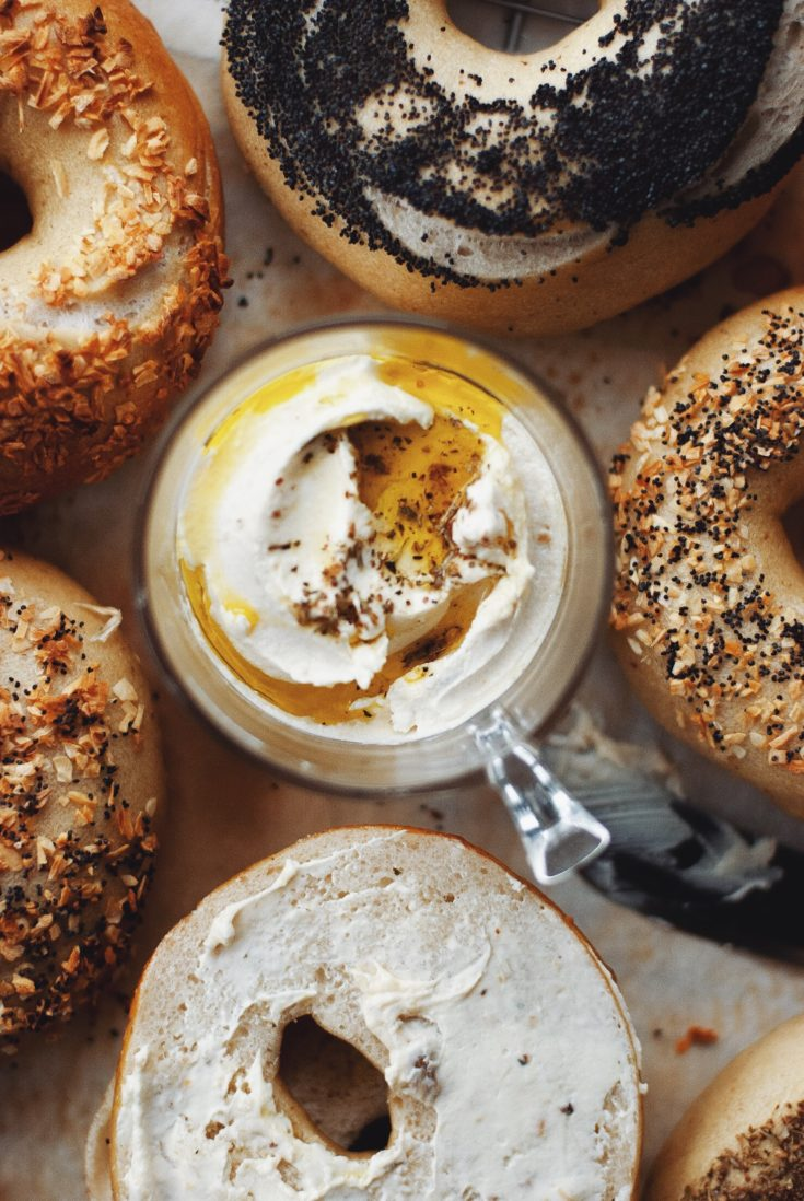 A jar of roasted garlic labneh surrounded by sourdough bagels.