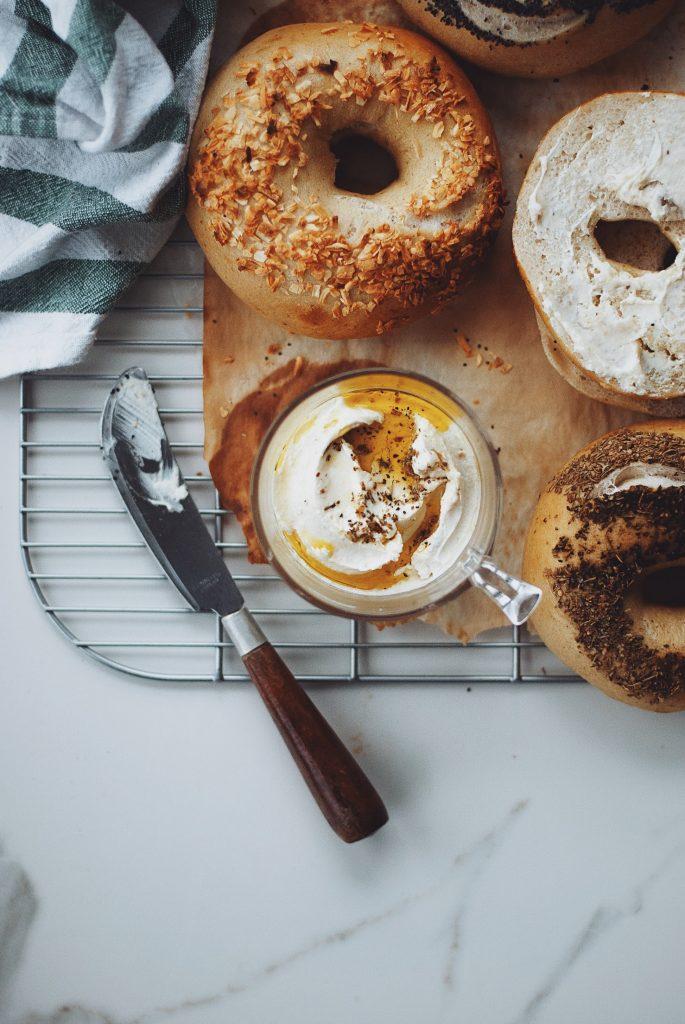 Overhead shot of bagels with a jar of roasted garlic labneh.