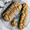 Braided rosemary rye bread on marble background with rosemary in upper corners