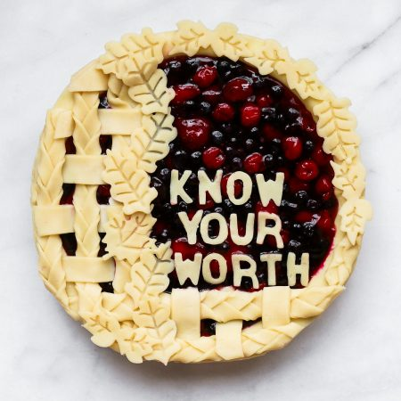 "Overhead image of a half lattice fruit pie with cut out leaves and the words ""know your worth"" in top in dough cutouts."