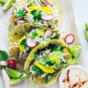 Overhead close-up shot of 3 Crispy Baked Baja Fish Tacos with Chipotle Mayo lined up with various toppings around them.