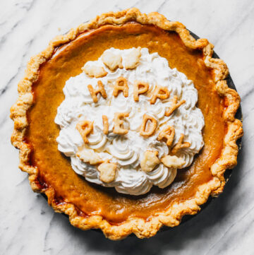 """Pumpkin pie with whipped cream topping and pie crust text saying """"Happy Pie Day""""."""