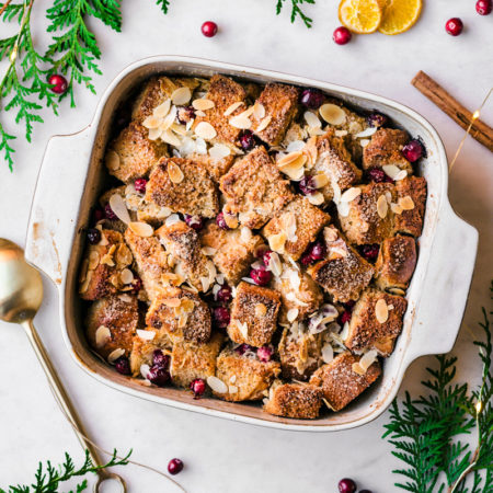 White wine bread pudding in a baking dish surrounded by greenery, oranges, and cinnamon sticks.