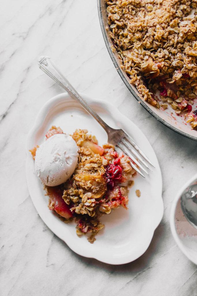 Overhead of vegan apple cranberry crisp on plate with ice cream.