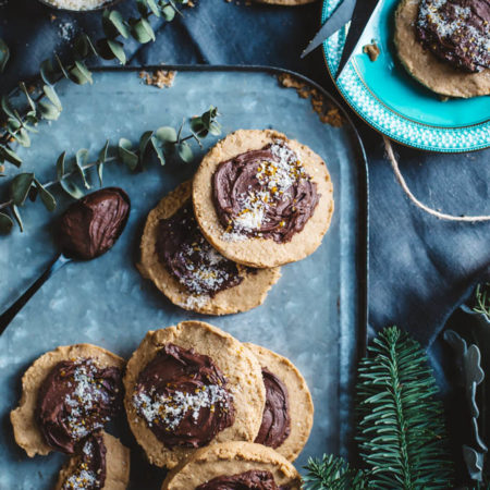 A pile of crumbly peanut butter cookies with chocolate ganache and banana sugar on a metal tray with greenery around.
