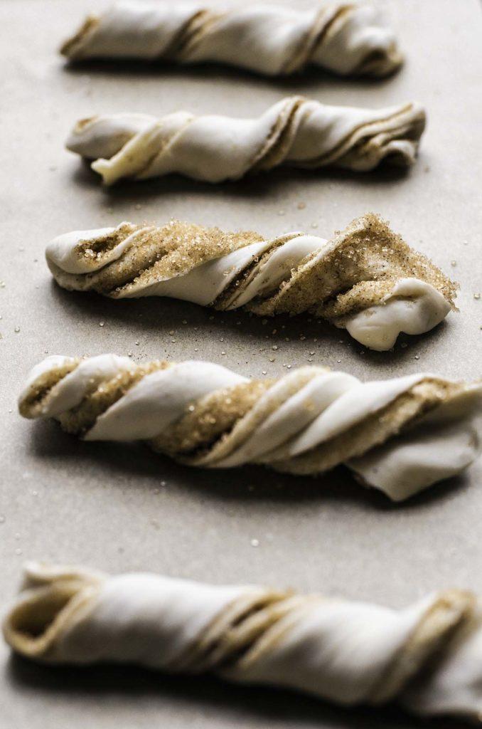 Unbaked cinnamon sugar puff pastry twists.
