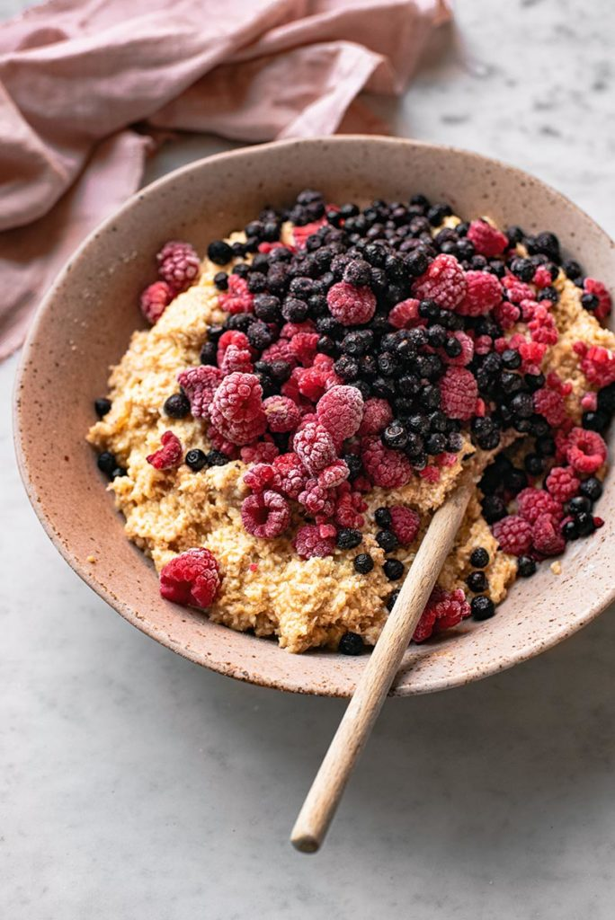 A bowl of muffin batter with berries.