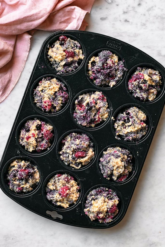 A muffin pan filled with batter for mixed berry muffins with toasted coconut.