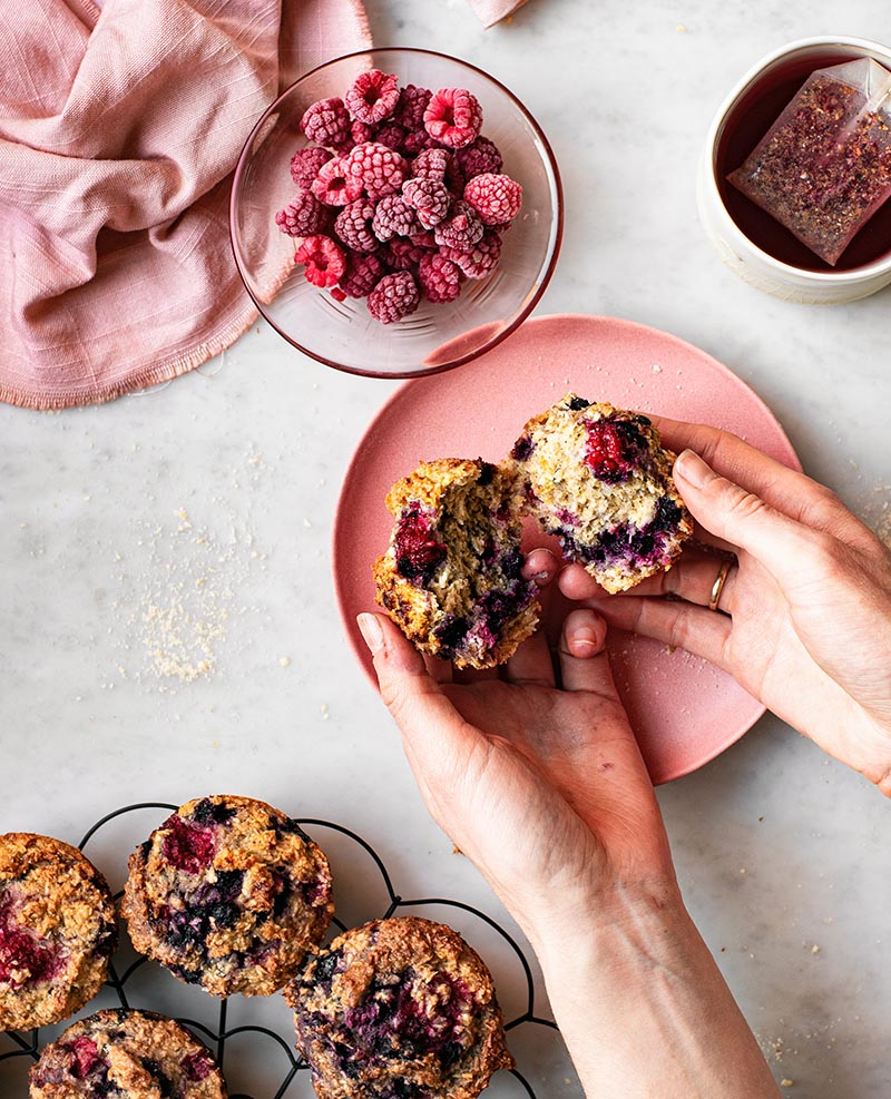 A hand breaking apart a muffin over a pink plate.