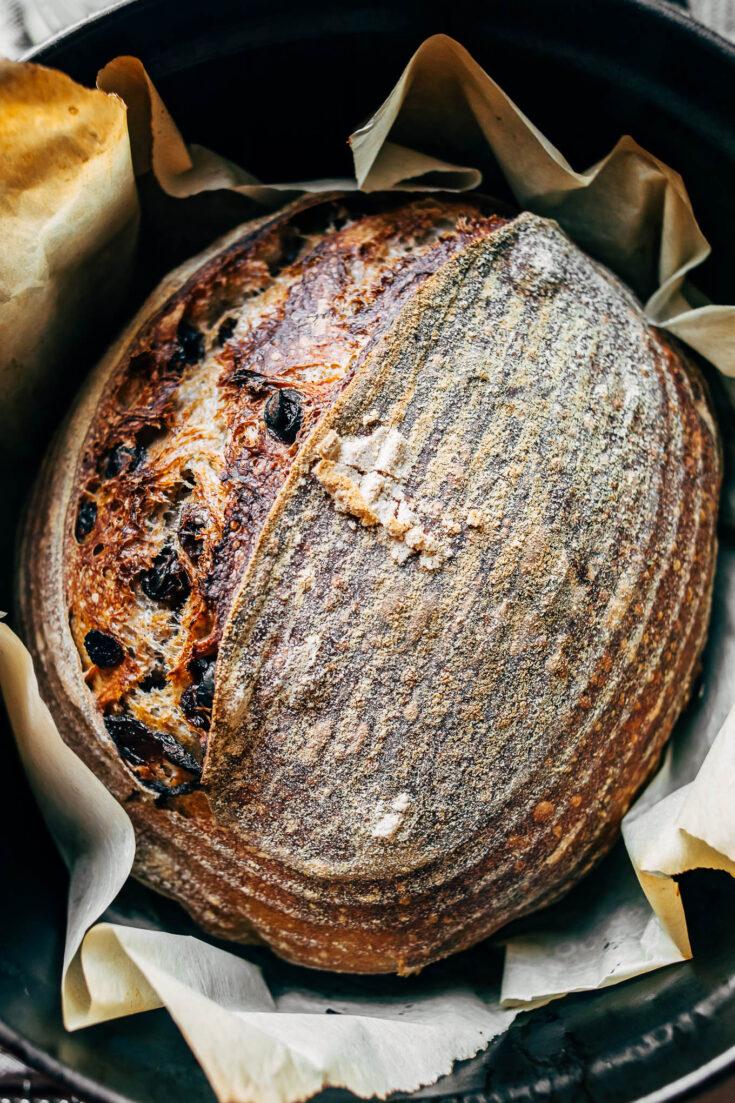 overhead image of a loaf of baked cinnamon raisin sourdough bread.