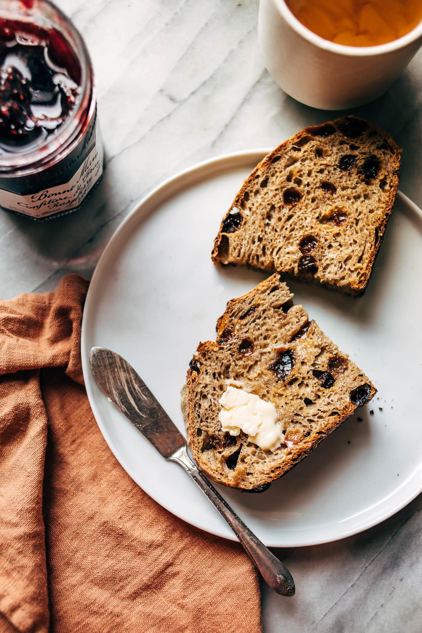 overhead image of two slices of cinnamon raisin sourdough bread on a white plate.